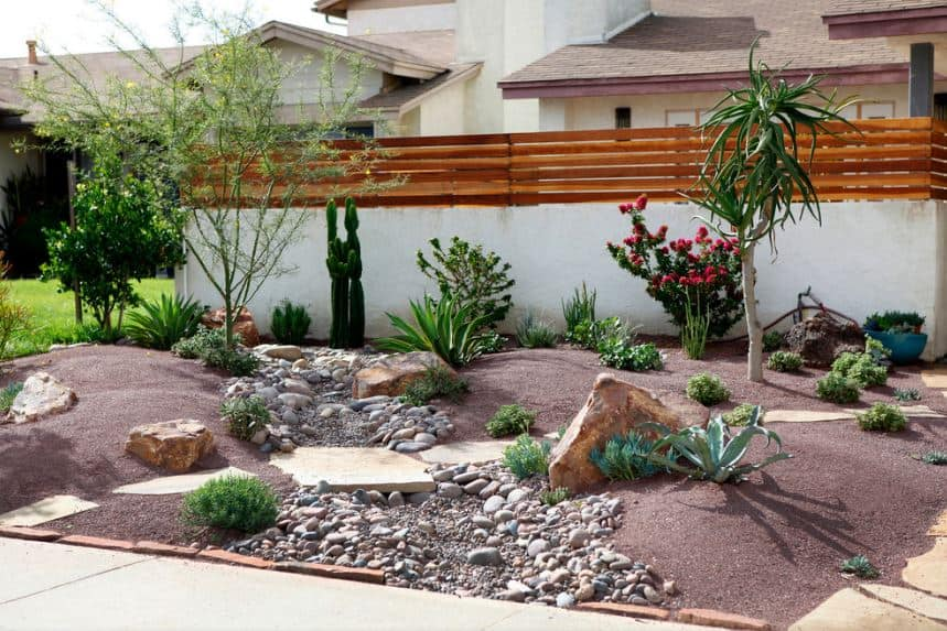 The small plot in front of this house's white concrete fence is filled with Southwestern-style landscaping that appears as if a square of desert land was cut out and transferred to this area. It has a wide variety of desert plants and decorative rocks as well as a small dried-up stream.