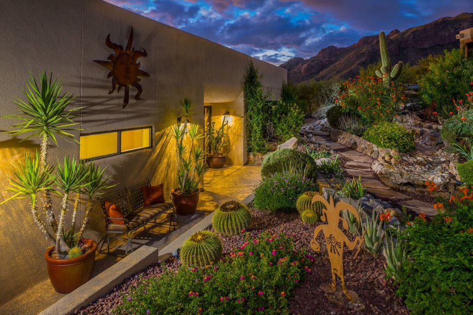 The earthy and textured exterior walls of this home is warmed by the yellow lights from the wall lamps that also give accent to the Southwestern-style landscaping of the backyard. The various rock formations are adorned with different cacti and succulents along with beautiful flowering plants.