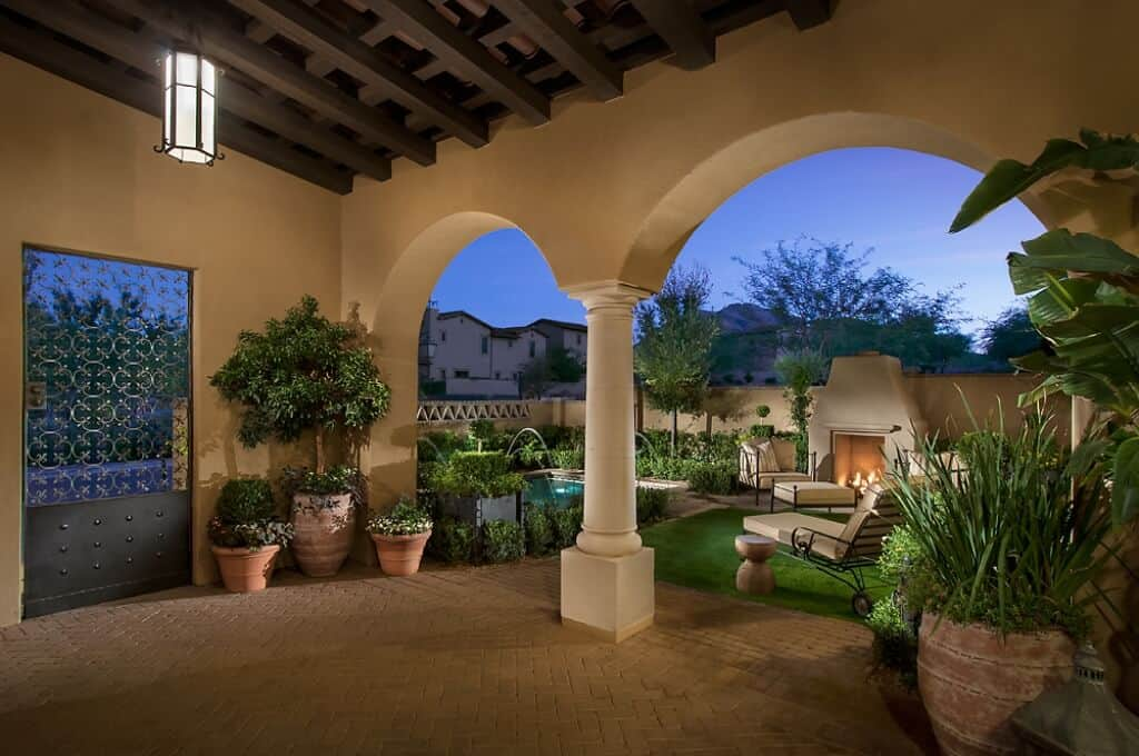 This is the open area that leads to the poolside through a couple of arched entryways flanked by various potted plants with terracotta pots that go well with the patterned walkway that transitions to a carpet of grass at the seating area warmed by an outdoor fireplace.