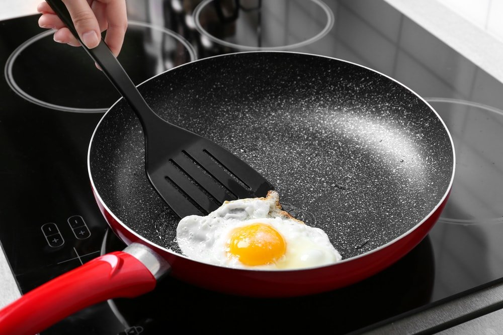 Frying an egg with a spatula.