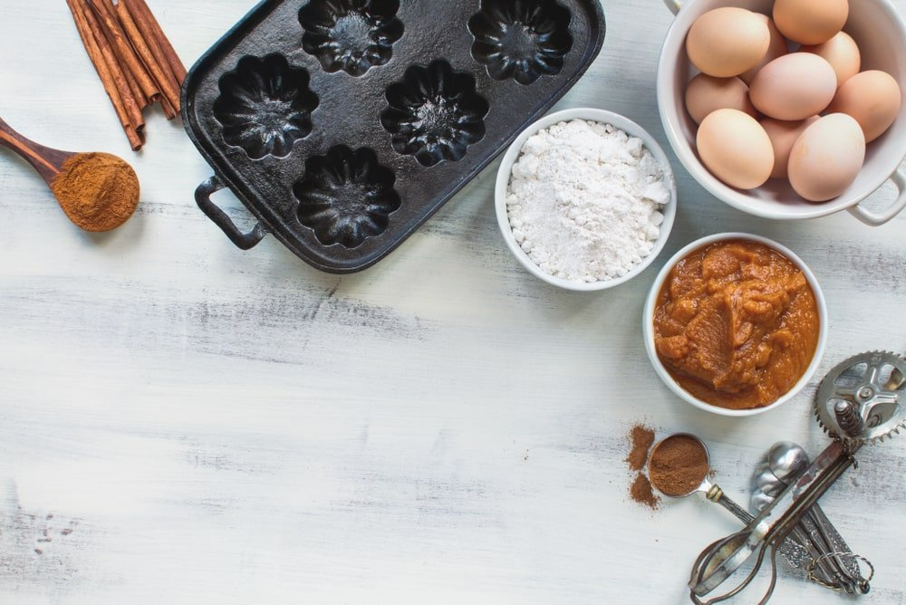 Empty cast iron muffin pan with ingredients.
