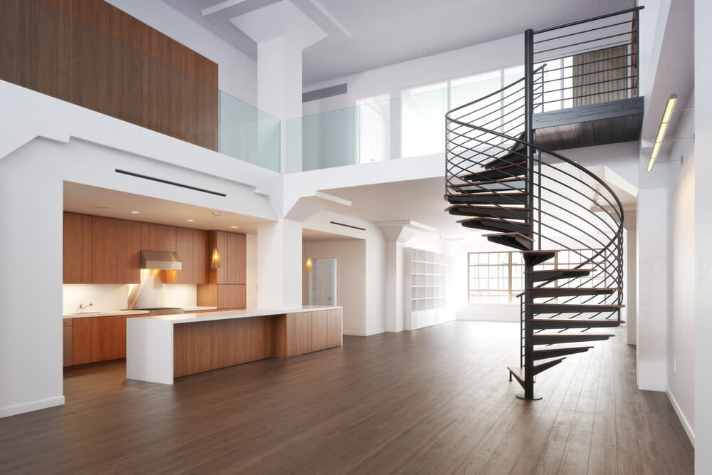 An empty house featuring white walls and hardwood floors, along with a two-storey ceiling. The home features a spiral staircase that looks so modish.