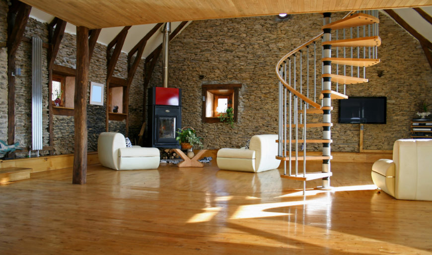 A large living space featuring hardwood floors, stone walls and a wooden ceiling. The area features comfy seats and a spiral staircase with hardwood steps.