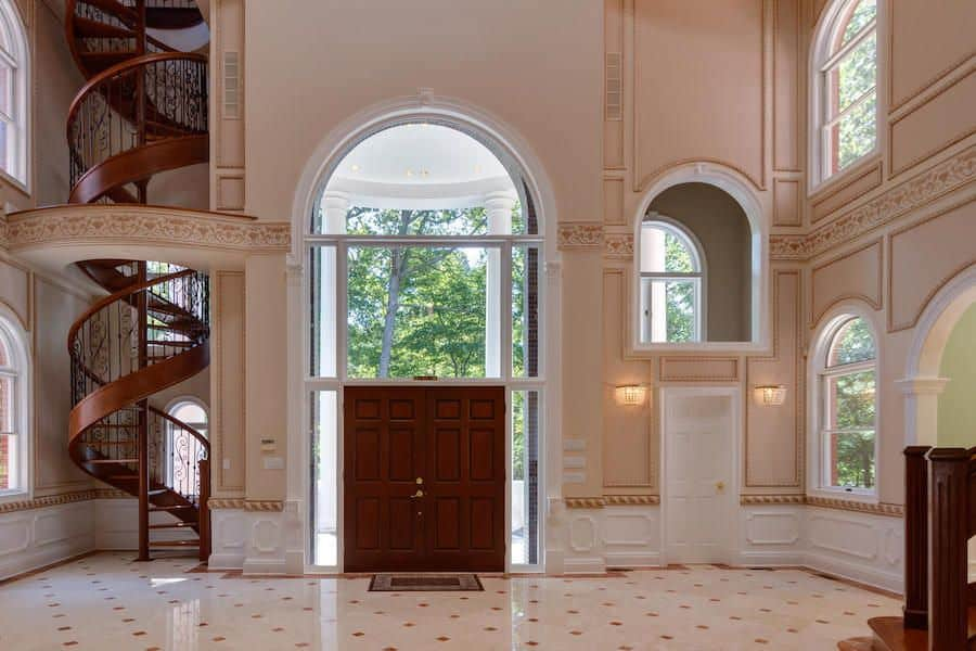 A large foyer boasting elegantly designed walls and tiles floors. It has a high ceiling, together with a stunning wooden spiral staircase in the corner.