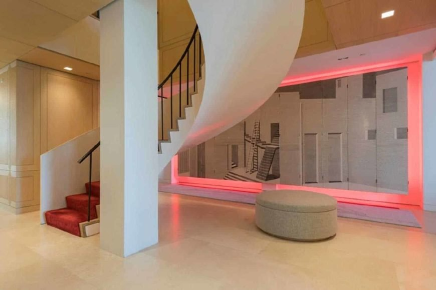 Contemporary home boasting a spiral staircase featuring red carpet steps. The home also features a large wall art with pink lighting.