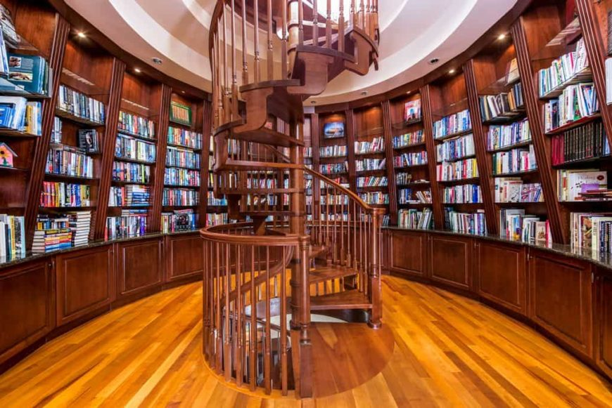 A gorgeous library with wooden bookshelves along with a stunning staircase made purely of hardwood.