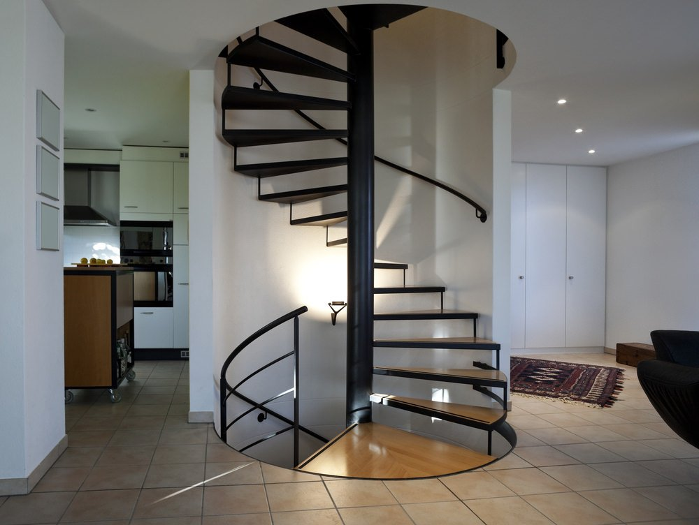 A focused look at this home's spiral staircase with white walls lighted by wall lights.