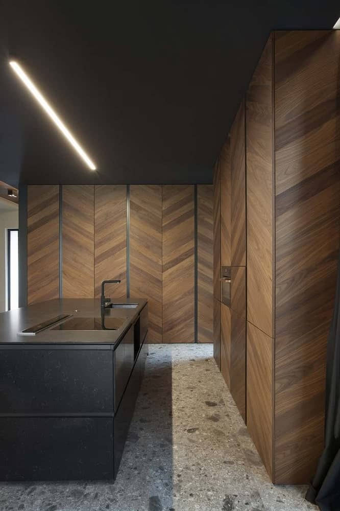 This is a simple kitchen with a black kitchen island surrounded by tall brown wooden cabinetry that dominates the walls with a herringbone pattern.