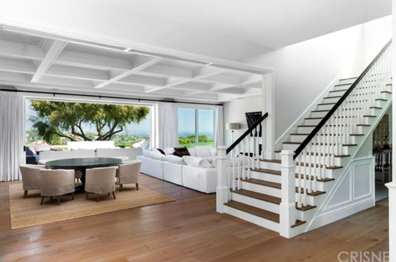A modern house featuring hardwood floors and a charming white coffered ceiling. The living space has a white sofa set and a round dining nook on top of an area rug. The home also offers a staircase with hardwood steps.