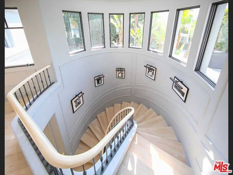 A gorgeous staircase surrounded by white walls. The staircase has hardwood steps matching the stair's handrail.