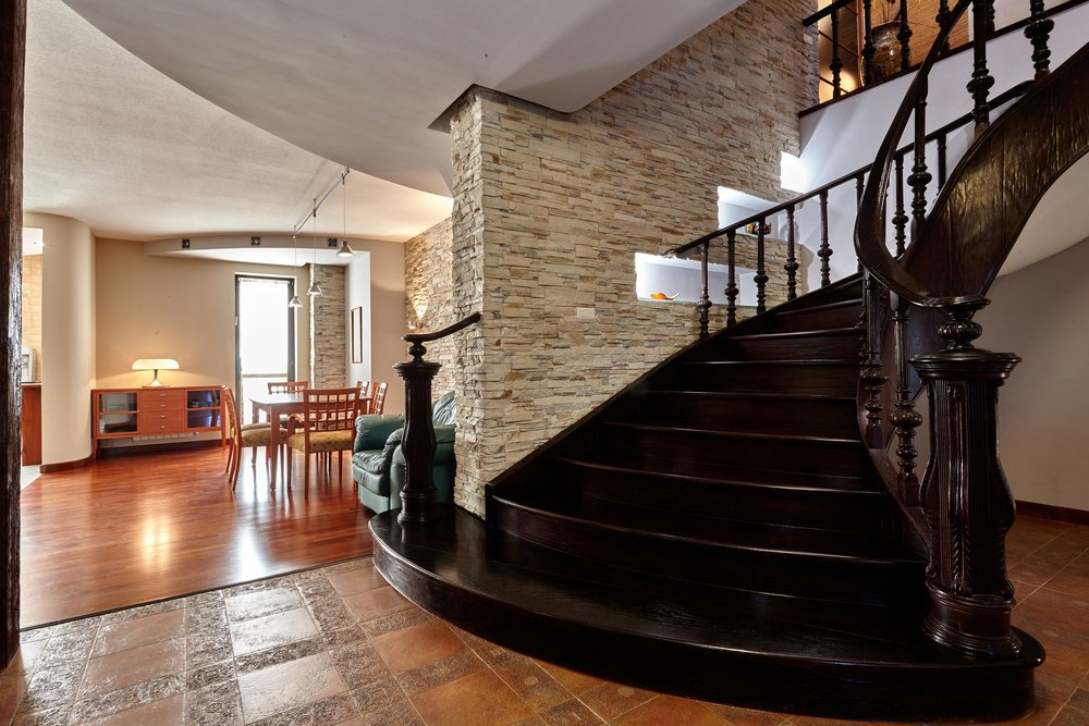 A close up look at this elegant staircase made of dark hardwood material. It has classy railings.