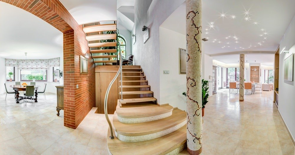 A focused look at this home's stylish staircase with hardwood steps. The home's living space is on the right side while the dining area is on the left.