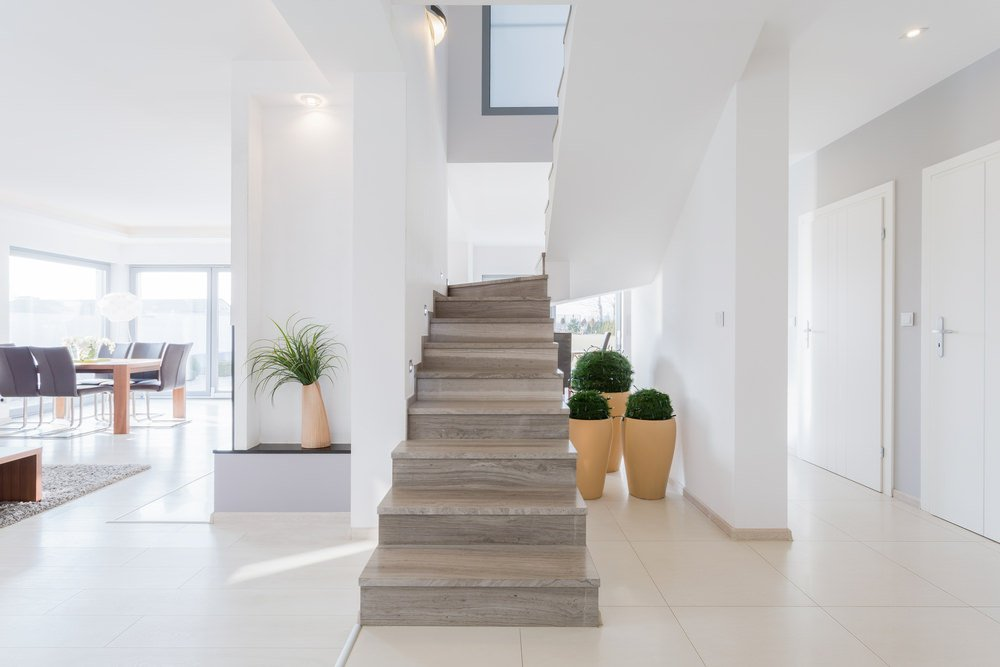 A focused look at this large modern house's staircase featuring hardwood steps and is surrounded by white walls and a white ceiling.