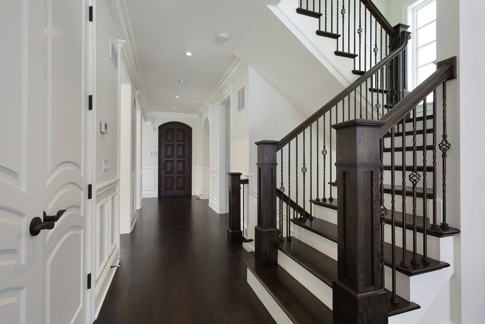 This home features dark hardwood floors matching the steps and the handrails of the staircase. The home also has white walls and ceiling.