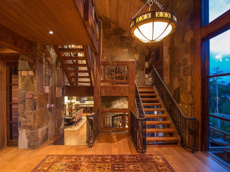 A rustic home boasting a staircase with hardwood steps surrounded by stone walls and a tall wooden ceiling, lighted by a large pendant lighting.