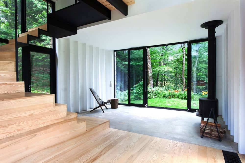 A contemporary home featuring a hardwood staircase leading to the home's second floor. The home features white walls and glass windows, along with a glass sliding door.