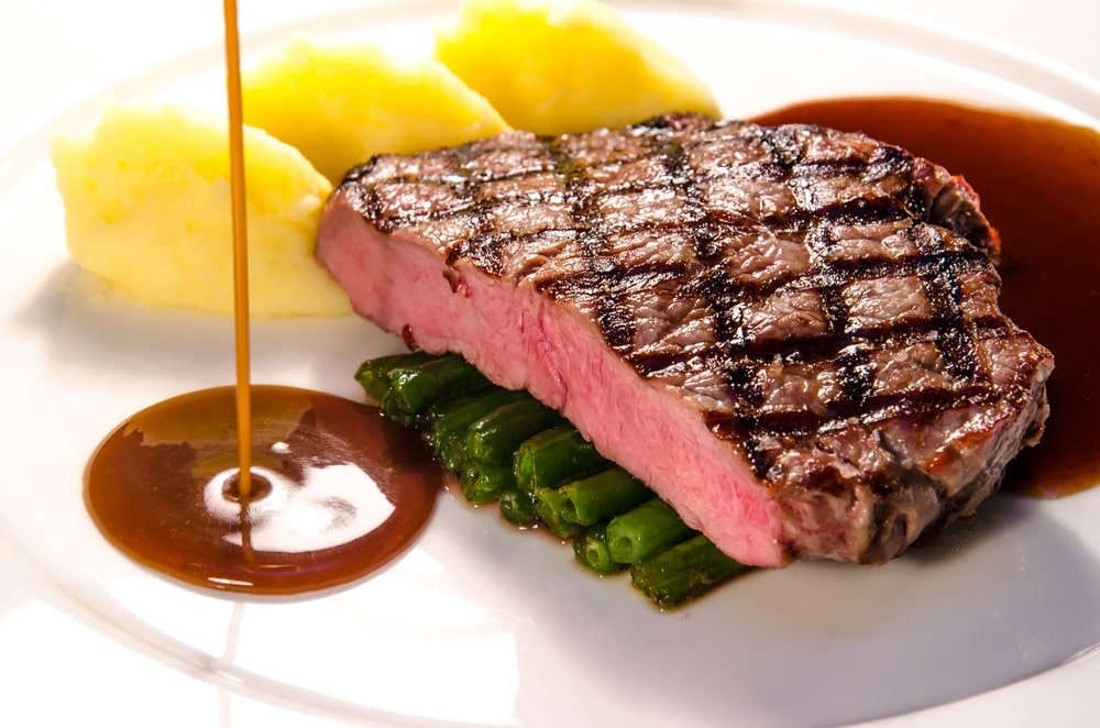 Steak sauce poured on the side of a steak dish.