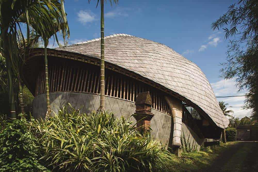 This is a close look at the house exterior with concrete base that supports the bamboo structures that extend to the dome ceiling that has earthy materials adorned by the tall tropical trees.