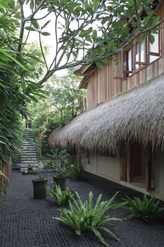 This is a close look at the house exterior showcasing one side of the house that has wooden exterior walls and rustic roofs made of dried palm leaves. These are all complemented by the Zen garden on the side with potted plants.