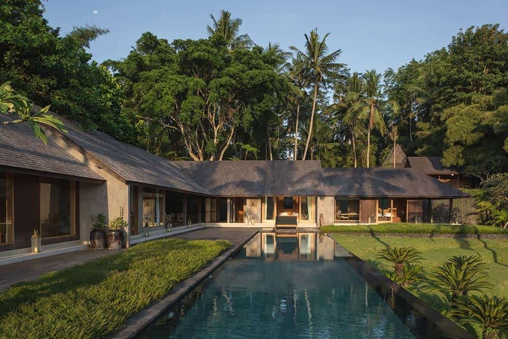 This is a back exterior view of the house with an L-shaped structure that has multiple doors and windows that open to the backyard landscape of grass lawns and a pool. These are all then complemented by the tall tropical trees in the background.