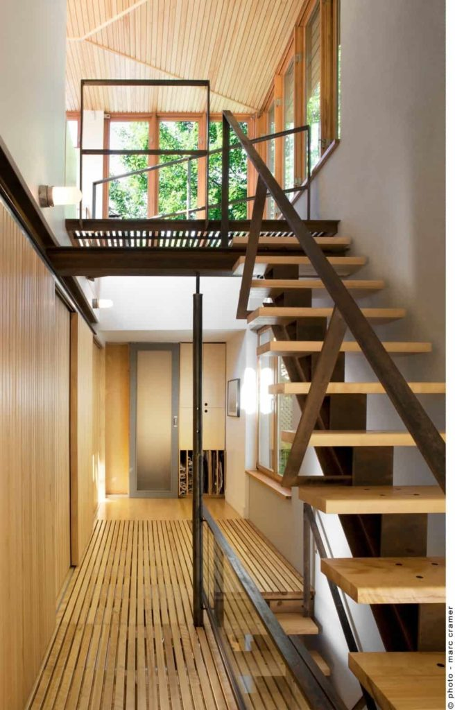 This is the view of the second level landing that leads the way to the staircase going to the third level. This staircase has wooden steps fitted with black iron railings and support that goes well with the wooden flooring and walls of the second floor landing.