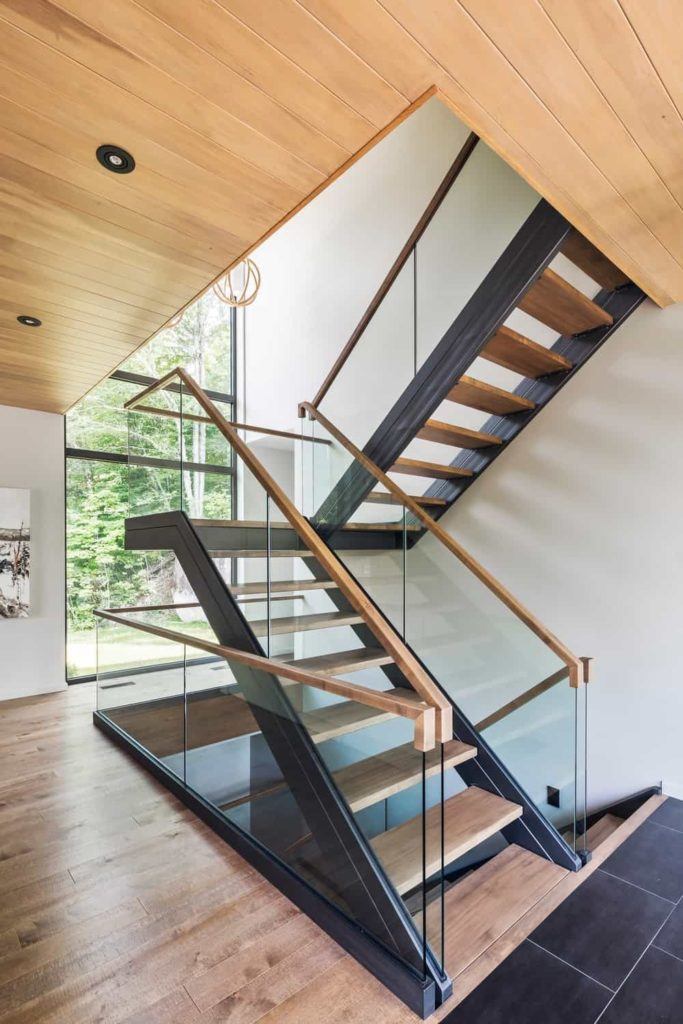 This second floor landing that leads to the upper floor is illuminated by the tall and narrow glass window. This is then adorned with a few wooden decorative pendant lights with the same wooden hue as the stairs, hardwood flooring and the ceiling.
