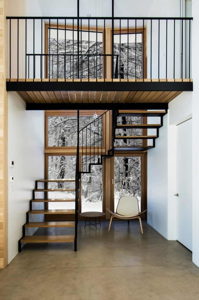 This view from the ground floor gives you a full look at the staircase structure to the second floor landing. This has dark iron support and railings contrasted by the wonderful snowy scenery outside of the tall and narrow glass window.