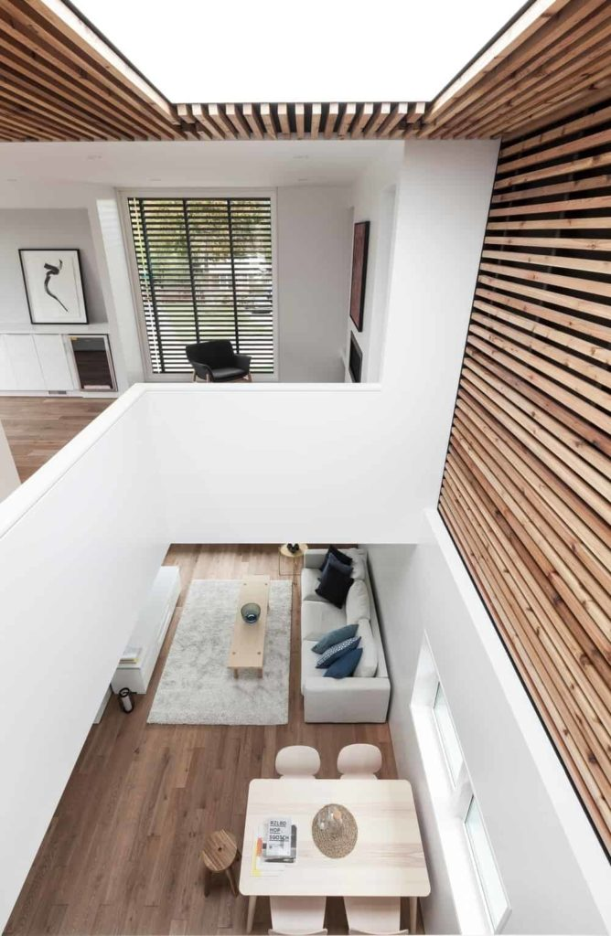 This area of the house has a large frosted glass skylight over the dining area two floors below the slat wood finish of the ceiling that extends to a part of the tall white wall. This brings an abundance of natural lighting for the light wooden dining table.