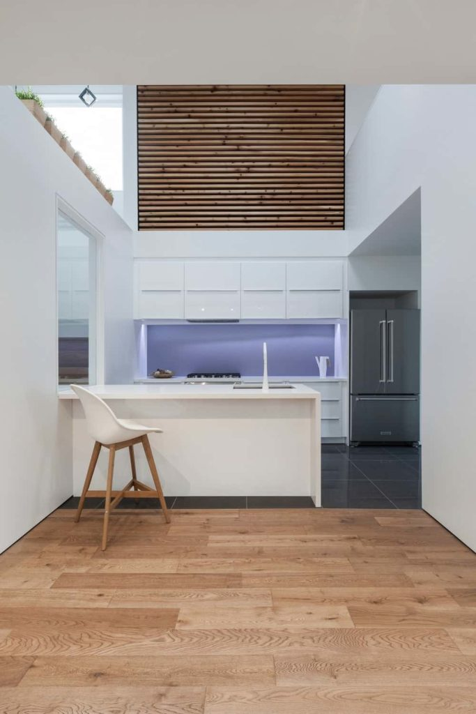 This is a small kitchen that compensated with a tall ceiling. This is paired with stark white walls that are adorned with small potted plants and a panel of slat wood. These white walls blend well with the modern cabinetry of the peninsula.