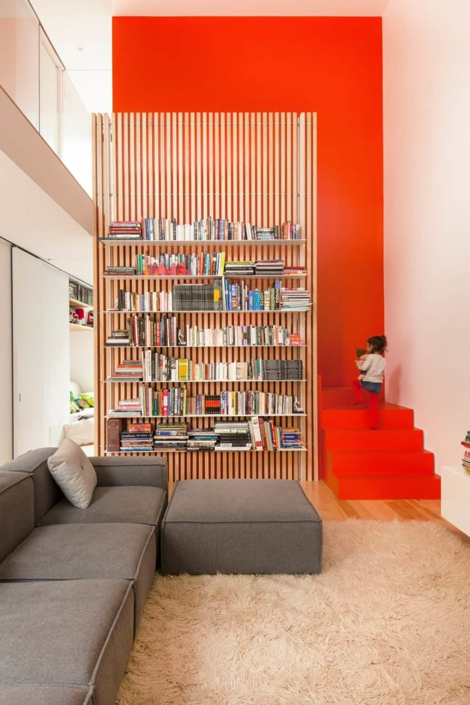 The gray L-shaped sectional sofa of this living room is adorned with a light pink furry area rug underneath. This is complemented by the hardwood flooring that transitions to a large wooden bookshelf and into a bright orange staircase leading to the second floor.