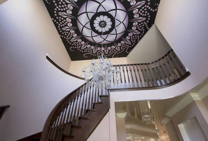 The ceiling above this staircase is the highlight of this area. This ceiling has complex elegant patterns that has a distinct chic quality. This is paired with a crystal chandelier hanging from the middle dome that stands out against the dark brown wooden staircase.
