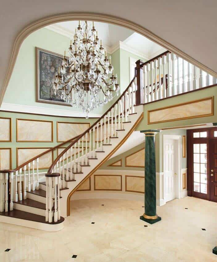There is a massive crystal chandelier hanging beside the white wooden staircase with dark brown wooden steps. These are complemented by the green pillars matching with the light green walls that have an elegant finish adorned with a colorful painting.