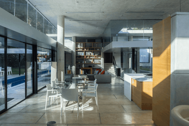 This is a great room that houses the living room area, dining room area and the kitchen under its high gray concrete ceiling. This pairs well with the concrete pillars as well as the glass walls and windows that bring in an abundance of sunlight to the flooring tiles.