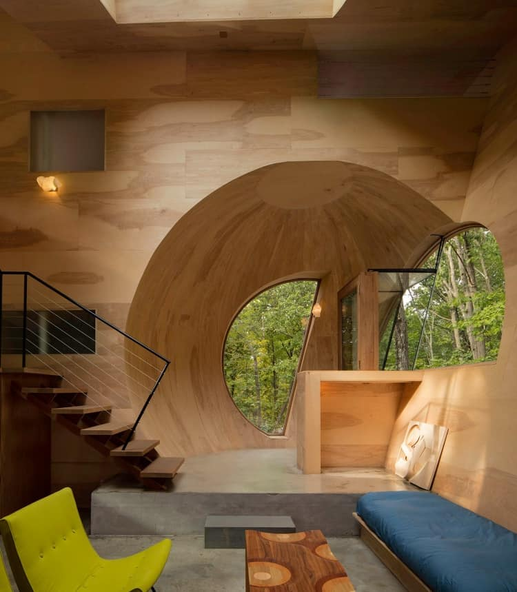This is a unique and quirky living room that has bare wooden walls with unusual nooks and domes that makes it look more like a playhouse. This makes it more so with the addition of the colorful chairs and bench cushion paired with a wooden coffee table on a gray concrete flooring.