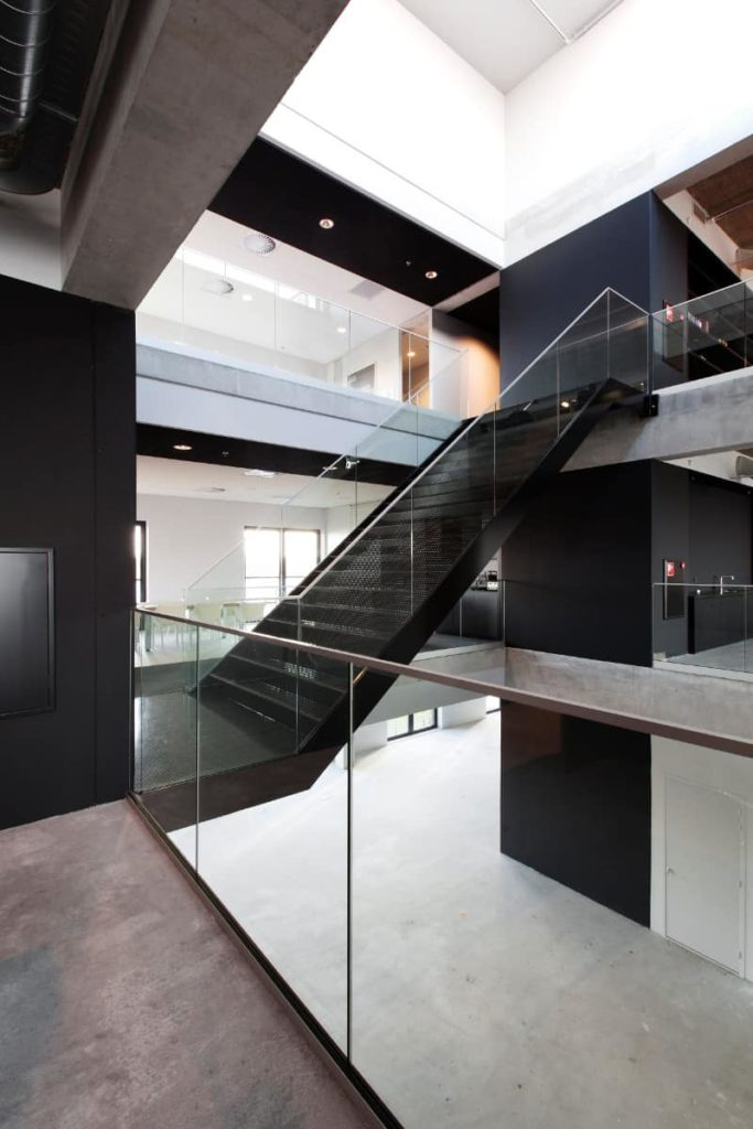 This is an ultra-modern house with a big middle area that is open from the ground floor all the way to the third floor and ultimately, the bright white ceiling above. Each floor of this home has glass on the sidesthat go well with the various black elements.