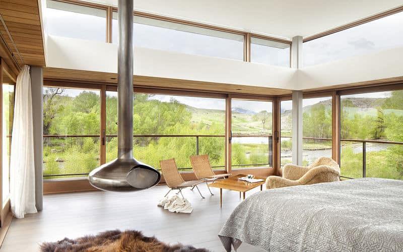 This awesome primary bedroom gives those who wake up on the gray bed a wonderful and bright morning wake up with its tall glass wall and additional transom windows near the high white ceiling. This is paired with a modern hanging fireplace for warmth and style.