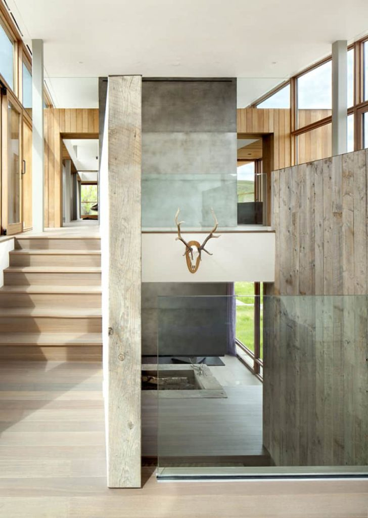 This is the second floor landing of this bright and airy home with a high white ceiling enhanced by the natural lights of the tall glass walls. This makes the light hardwood flooring and steps leading to the second floor seem like a shade lighter.