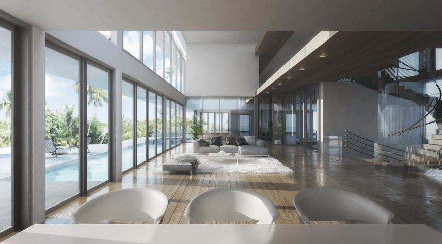 This is a large and modern great room with an open concept. This gives the living room area in the middle seem far bigger than it actually is. There is also a clear view of the outside through the tall glass walls as well as a view of the second floor.