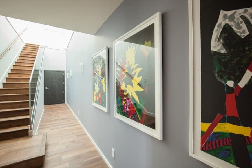 This is a hallway-type foyer with a dark wooden main door leading to a hallway with tall gray walls and narrow hardwood flooring compensated with a high ceiling. This is adorned with various colorful abstract paintings bringing color to the gray walls.