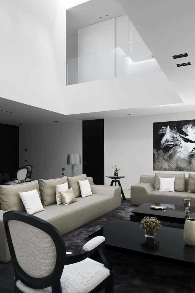 The middle part of this living room has a high ceiling that gives those sitting on the gray leather sofas a clear view of the second floor that has a half glass wall. This living room has a couple of pitch black coffee tables that go well with the black area rug.