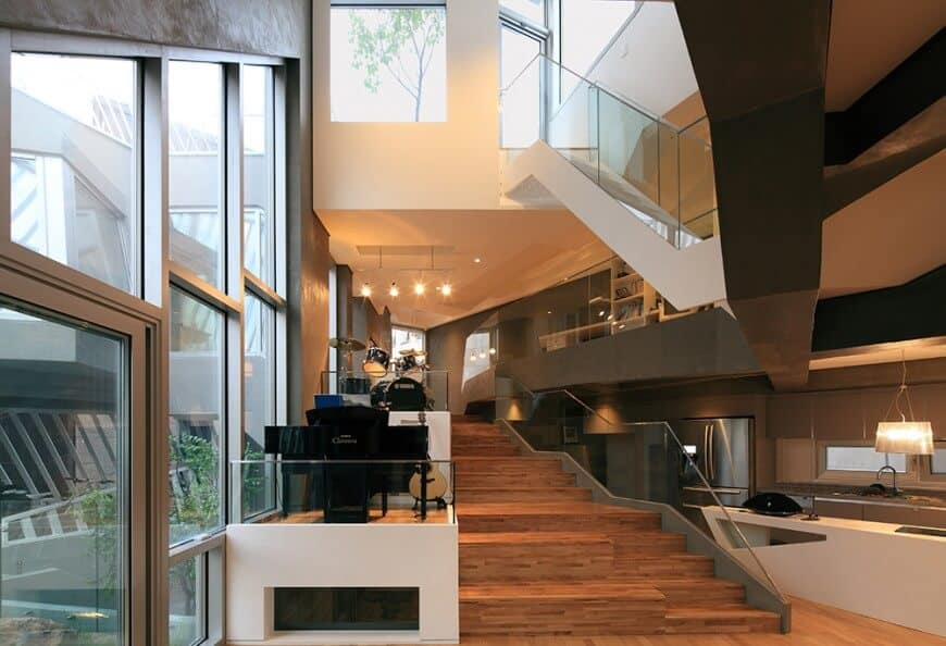 This modern home has the kitchen right by the wide staircase that leads to the second floor. This area has a tall white ceiling warmed by the yellow lights and brightened at the same time by the tall glass windows that dominate the gray wall where the musical instruments are displayed.