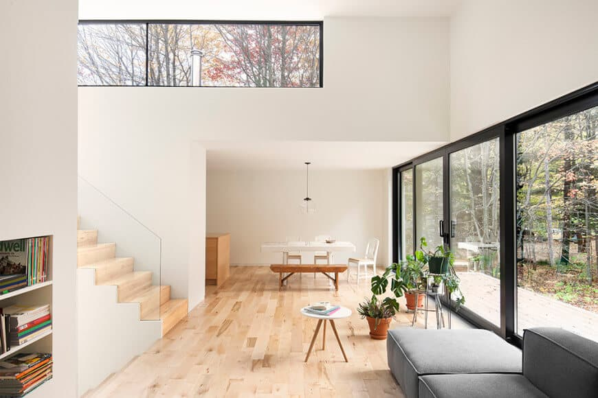 The brightness of the natural lights coming in from the glass doors and the transom windows are augmented by the white walls and white ceiling. This also brightens the light hardwood flooring from the living room area to the dining area at the far end.