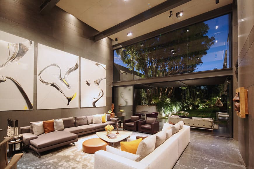 This wide living room appears larger with an open wall to the back porch that leads to the backyard. This is enhanced by a large transom glass window above the open wall giving a nice background for the simple gray L-shaped sectional sofa adorned with large paintings above.