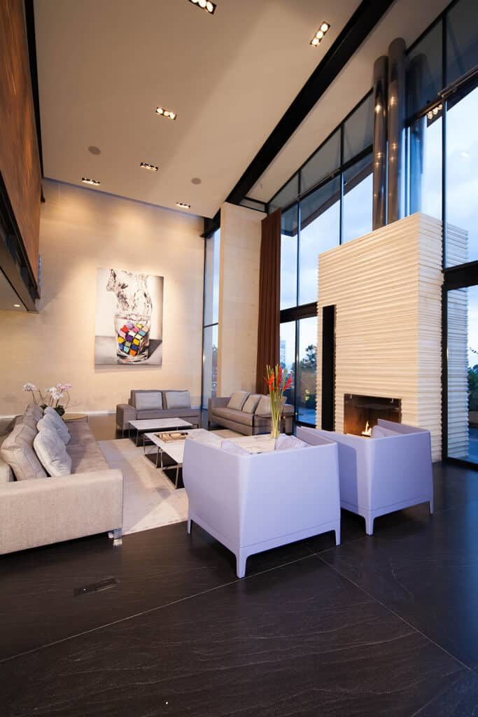 The highlight of this massive living room is the fireplace that is embedded into a textured beige column surrounded by tall glass walls reaching up to the high white ceiling that has recessed lights. This contrasts the black textured flooring tiles paired with a sofa set with different shades of gray.