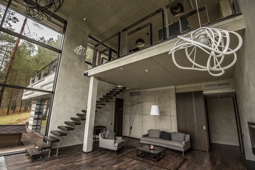 This charming Industrial-style home has concrete gray walls, pillars and high ceiling. This hangs a trio of decorative pendant lights that accent the walls. There is also a large standing lamp for the same effect standing beside the gray sofa set in the living room.