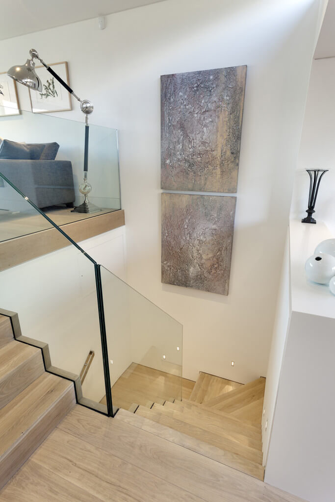 The light hardwood flooring of the second floor landing extends to the wooden steps of the staircase that is bordered with glass walls. This high ceiling area is adorned with a couple of colorful abstract paintings to stand out against the white walls.