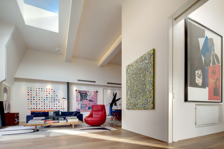 This is a spacious and bright living room with white walls that are illuminated by the brilliant skylight from the white tall ceiling. The white walls are contrasted by the colorful upholstered furniture as well as colorful wall-mounted artworks.