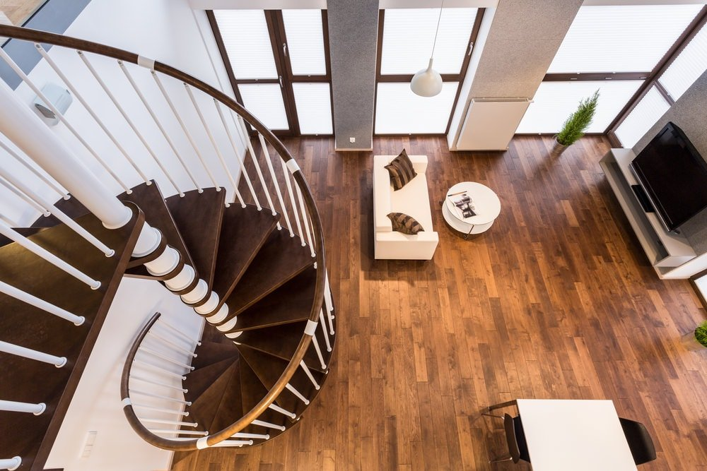 This is a view from the second floor landing looking down at the brown wooden spiral staircase that pairs well with the hardwood flooring below. This makes the light beige tone of the sofa stand out as well as the round white coffee table.