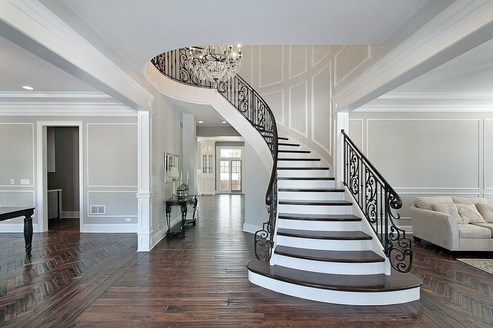 This is a home with bright gray walls and white molding that pairs well with the crystal chandelier hanging in the middle of the tall ceiling area of the stairs. These are contrasted by the dark hardwood flooring, wrought iron railings and the steps of the stairs.