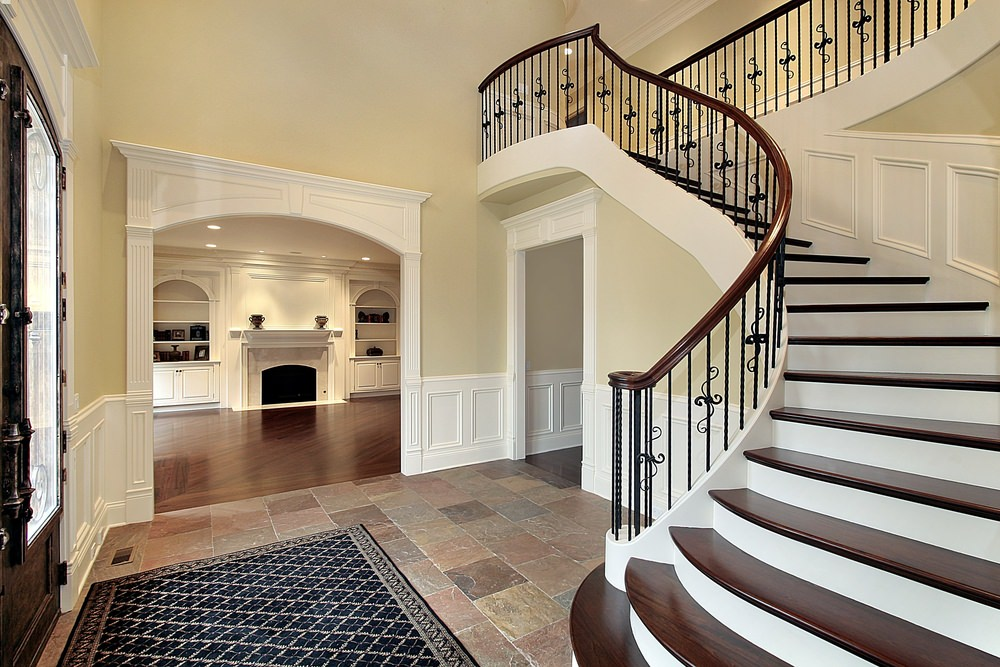 The cheerful light tone of the walls of this home is augmented by the white wainscoting that extends to the frames of the arched entryway and passages. This is further elevated by the earthy tones of the flooring that transitions to hardwood flooring.